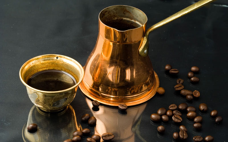 Turkish coffee sitting in a cup and next to is a gold coffee pot called a cezve