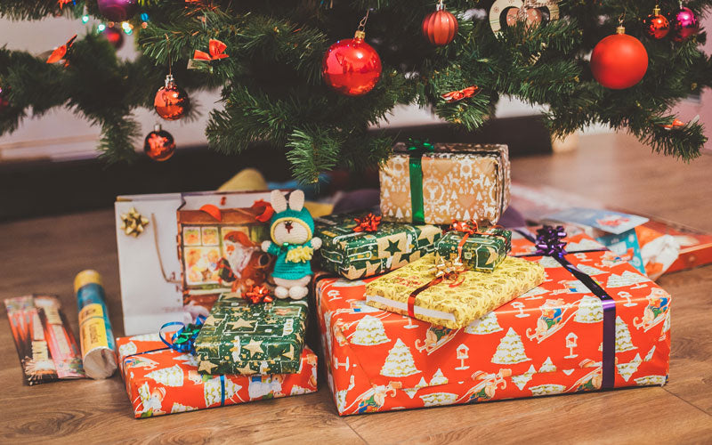 A close up photo of wrapped Christmas presents sit under a Christmas tree