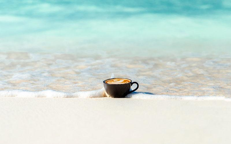 A cappuccino in a mug sits on a beach near the water
