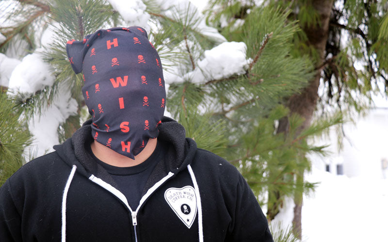 A male wearing a black and red bandana that covers his entire face, including his eyes