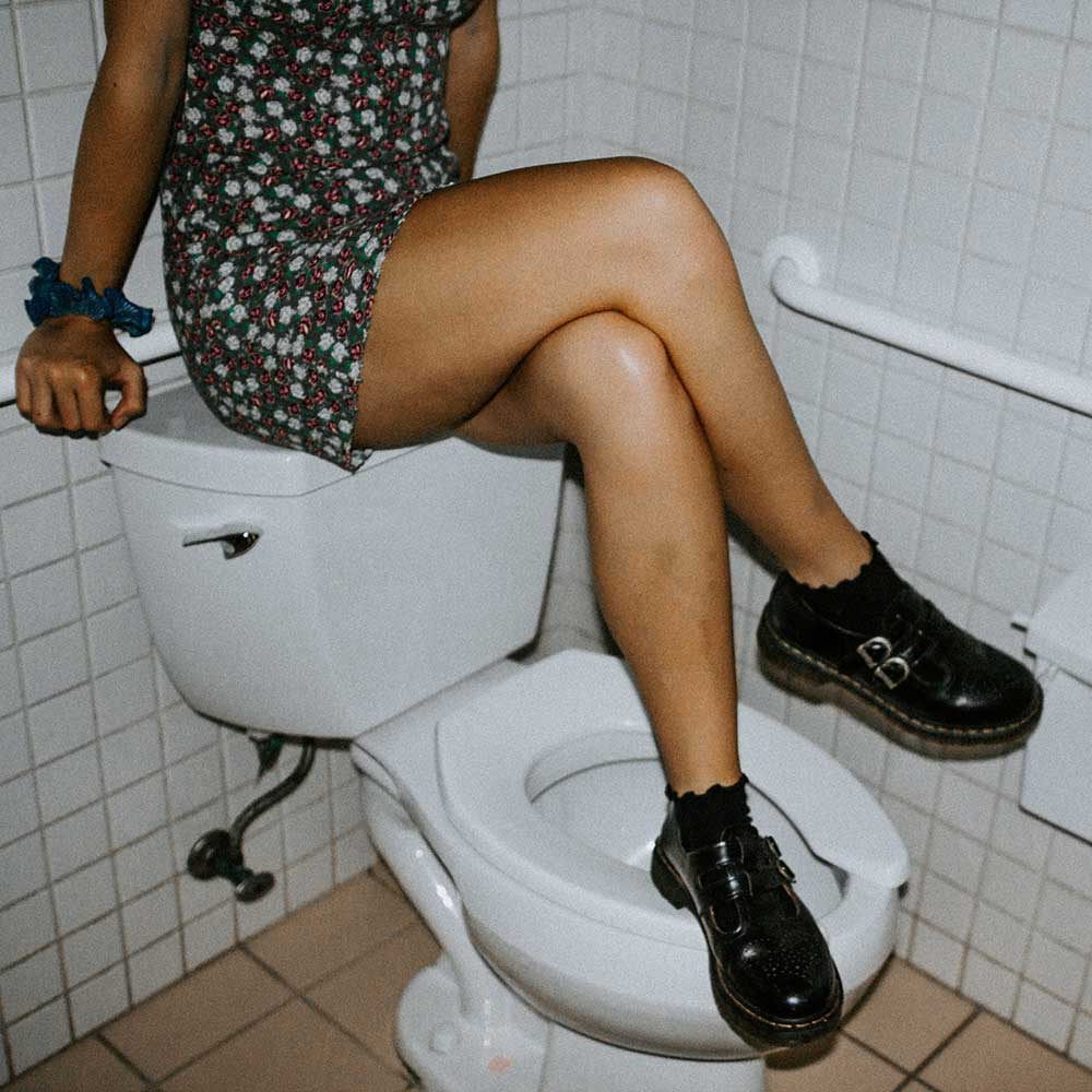 A woman in the bathroom sitting on top of the toilet bowl.