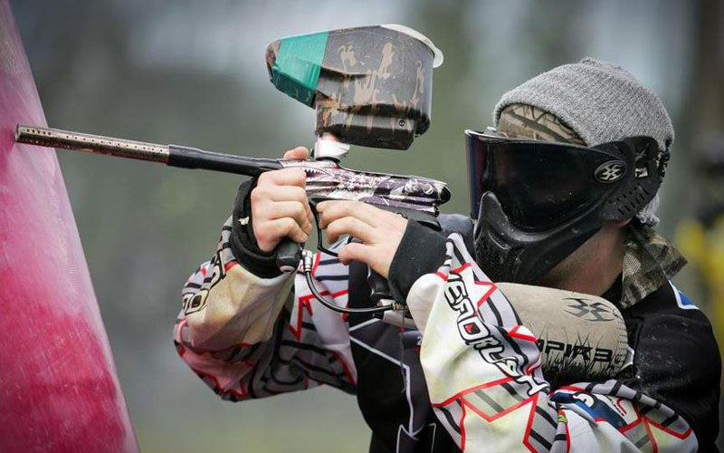 A photo of a man, Will Critcher, wearing a paintball uniform, goggles, and holding a paintball gun