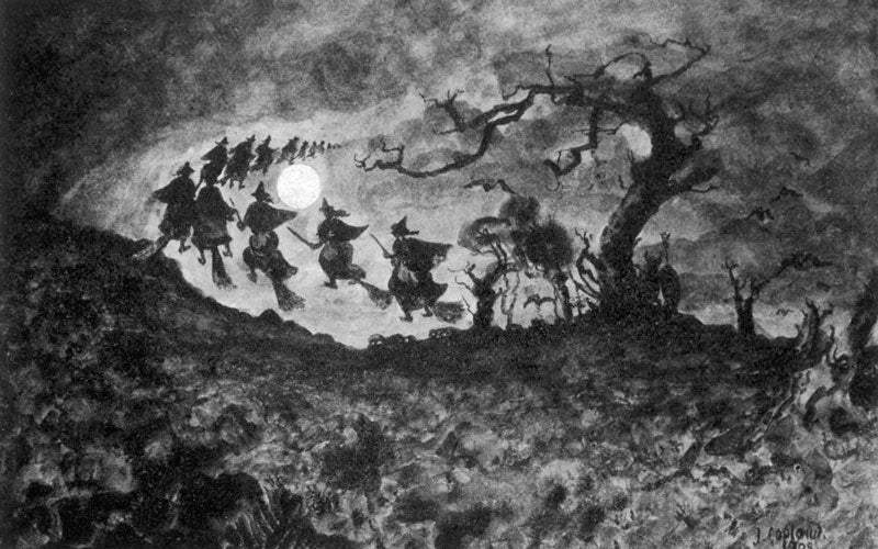 A black and white photo of witches flying on broomsticks