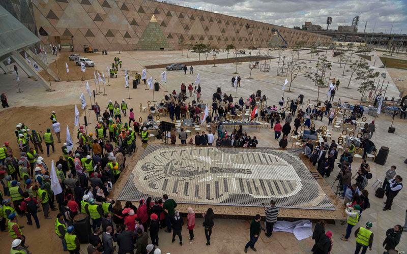 People stand around the world's largest coffee cup mosaic in Egypt, which depicts King Tutankhamun burial mask