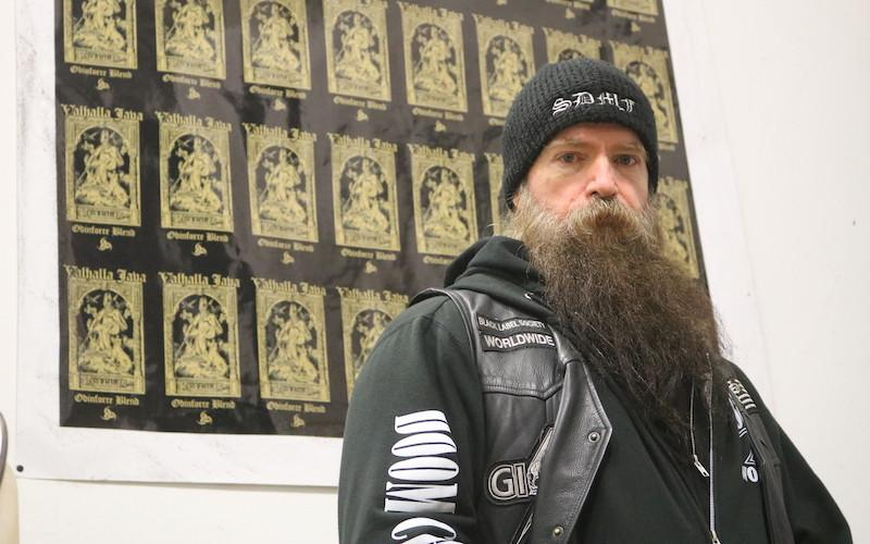 Guitarist Zakk Wylde stands in front of a wall with the black and gold Valhalla Java coffee logo