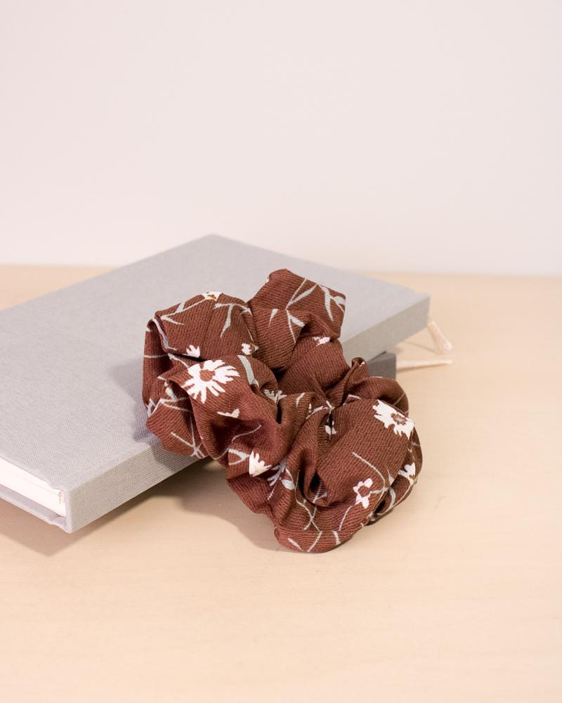 Daisy floral patterned scrunchie in brown colour style, displayed on notebooks