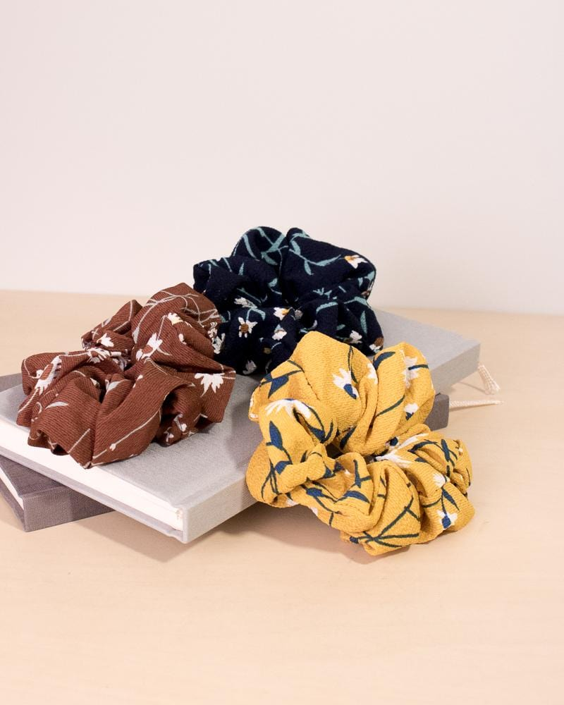 Daisy floral patterned scrunchie in brown, navy, and yellow colour styles, displayed on notebooks