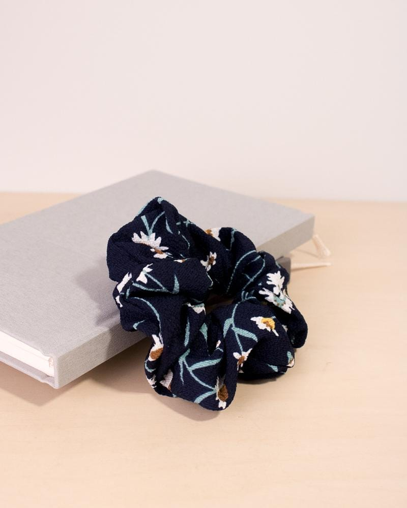 Daisy floral patterned scrunchie in navy colour style, displayed on notebooks