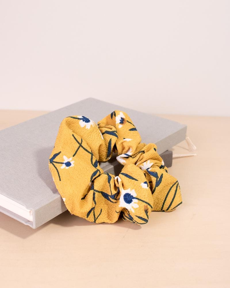 Daisy floral patterned scrunchie in yellow colour style, displayed on notebooks