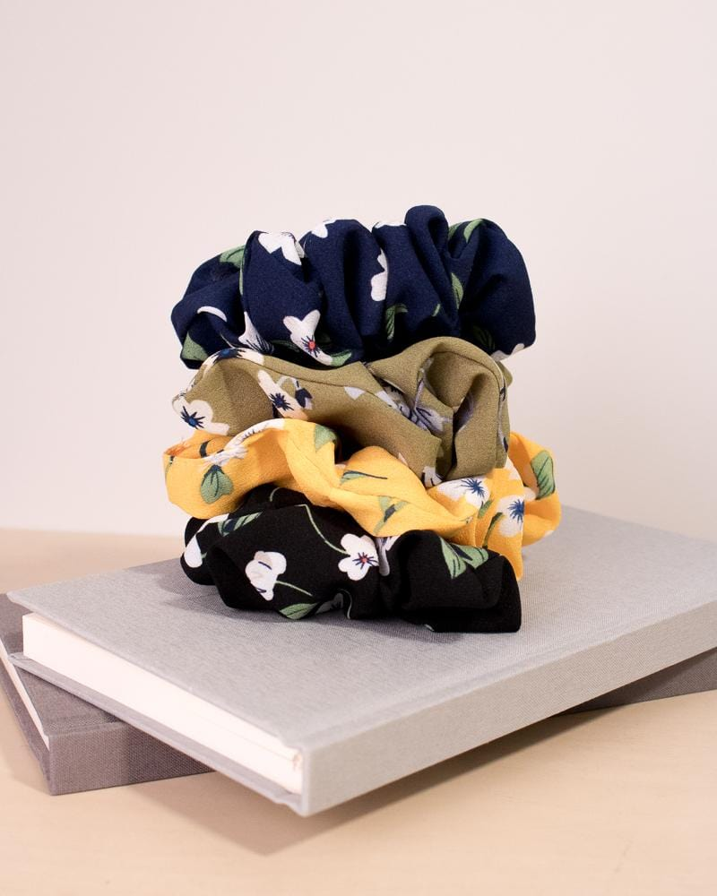 Floral Pansy Pattern Scrunchie with navy, olive, mustard and black colour styles, displayed on notebooks