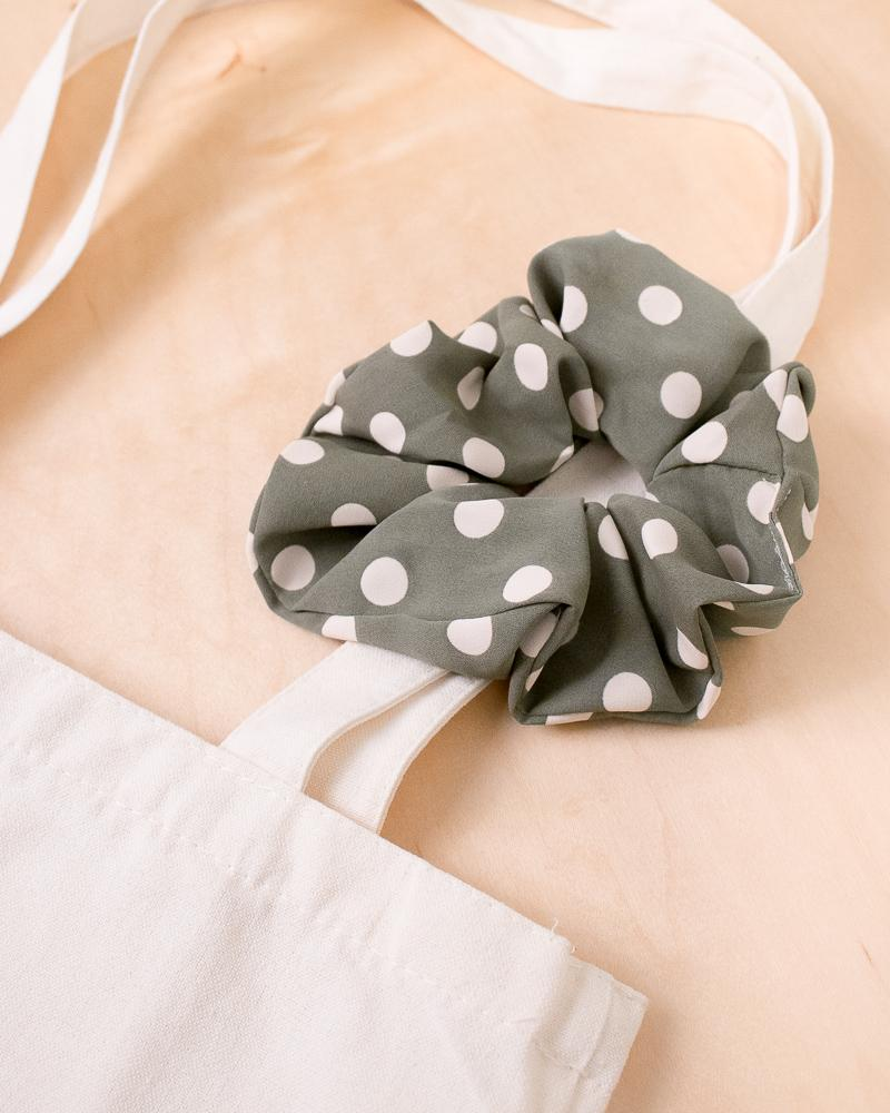 large polka dot scrunchie in army green colour style displayed on canvas tote bag