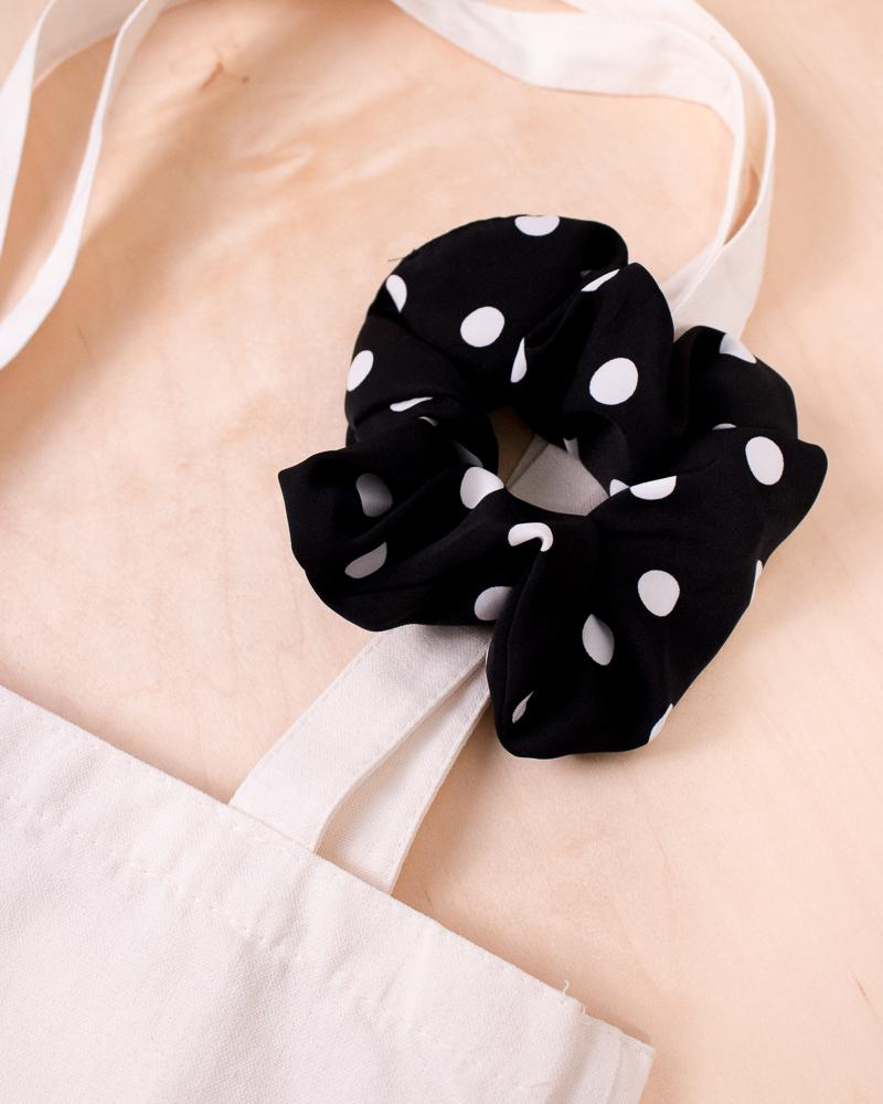 large polka dot scrunchie in black colour style displayed on canvas tote bag