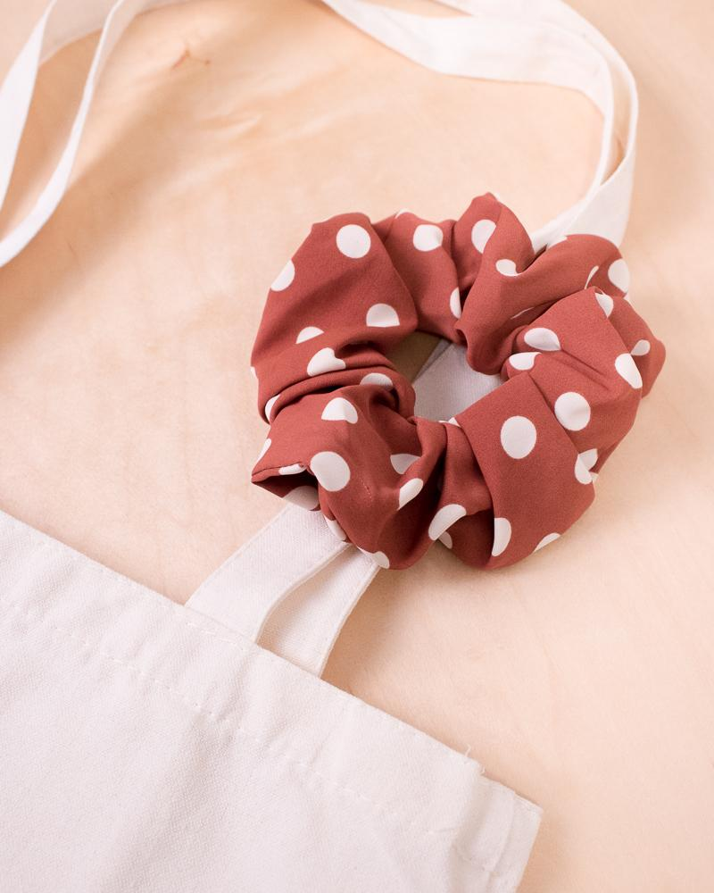 large polka dot scrunchie in coral colour style displayed on canvas tote bag
