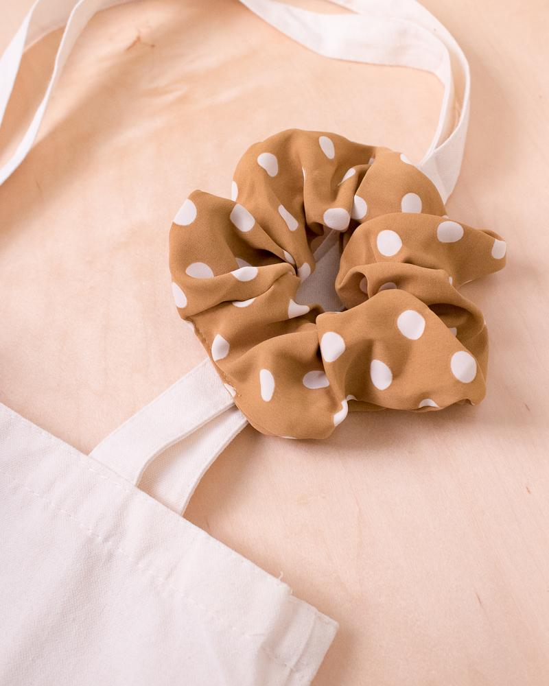 large polka dot scrunchie in mustard colour style displayed on canvas tote bag