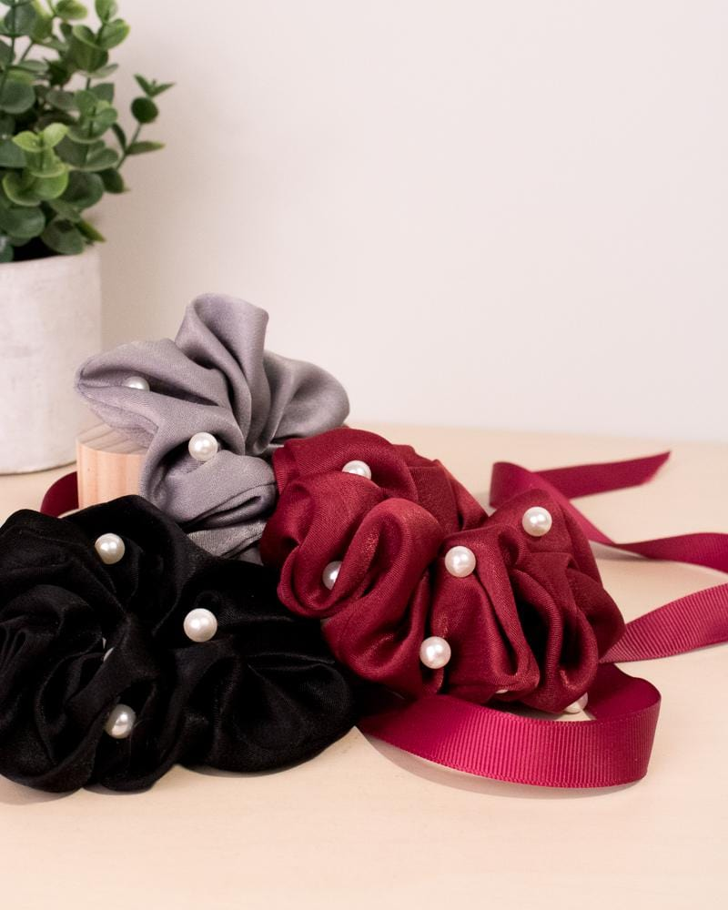 Pearl silk scrunchie in black, grey and red colour styles, displayed with ribbon