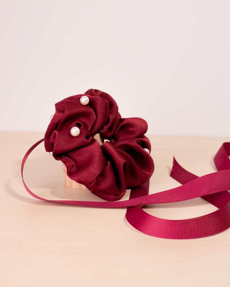 Pearl silk scrunchie in red colour style, displayed with ribbon