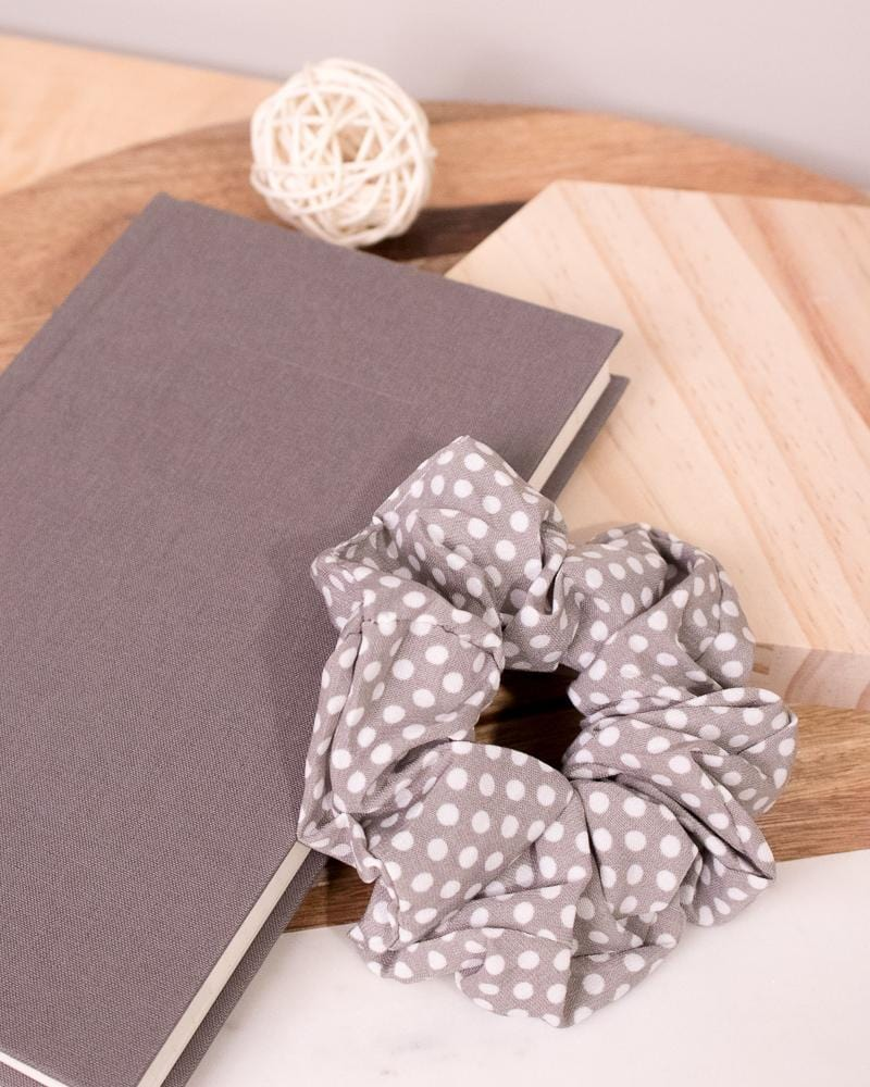 Polka Dotted Scrunchie in grey colour style displayed on notebook
