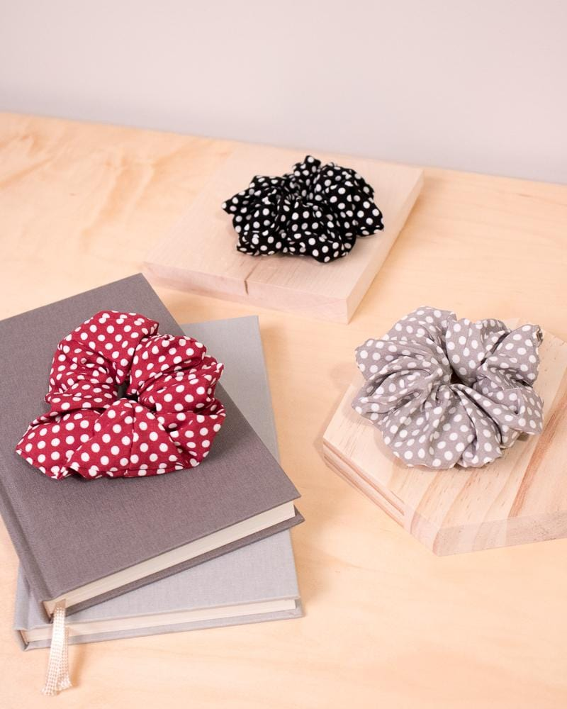Polka Dotted Scrunchie Red, Black and Grey colour styles displayed on notebooks