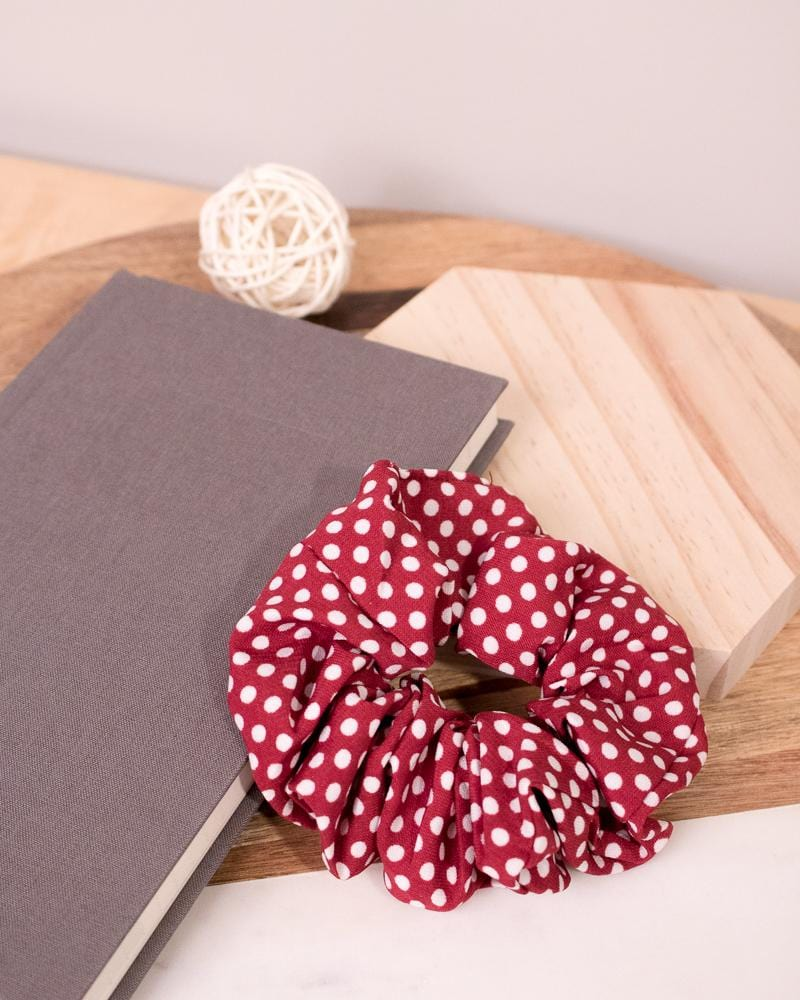 Polka Dotted Scrunchie in red colour style displayed on notebook