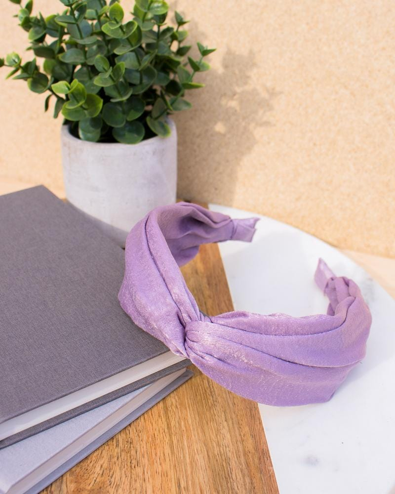 satin knotted headband in lilac colour style, displayed on notebooks