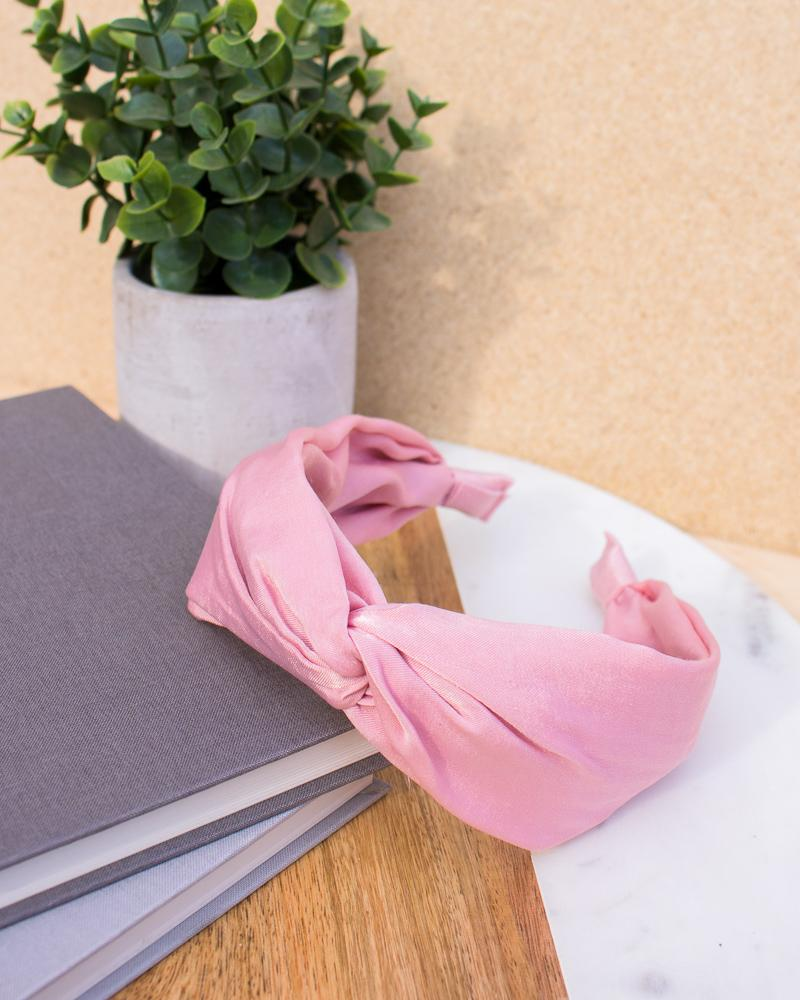 satin knotted headband in pink colour style, displayed on notebooks