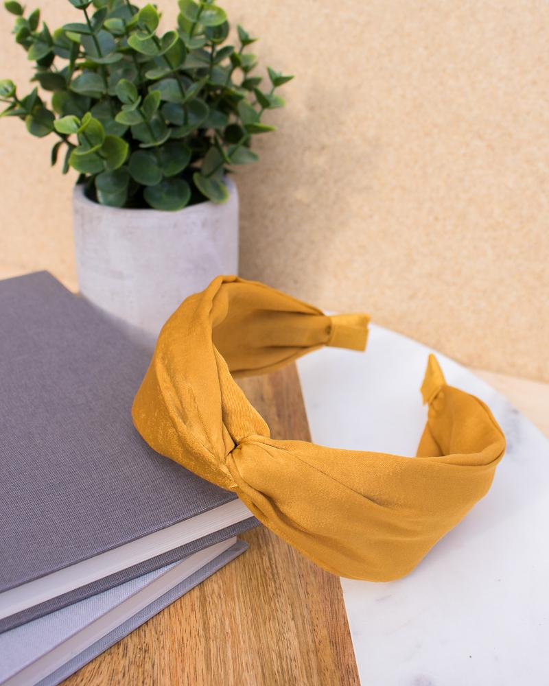 satin knotted headband in yellow colour style, displayed on notebooks