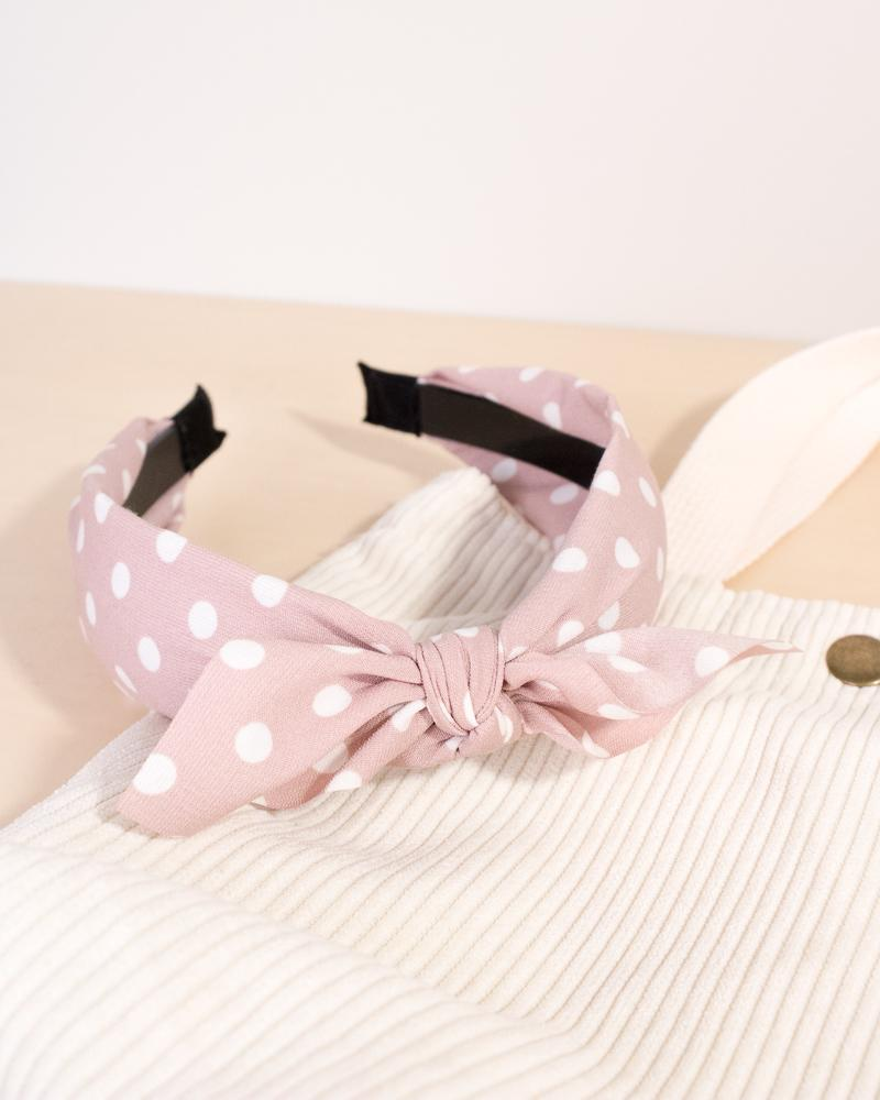 spotted bow headband in blush pink colour style, displayed on tote bag