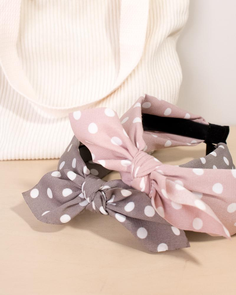 spotted bow headband in grey and pink colour styles, displayed on tote bag