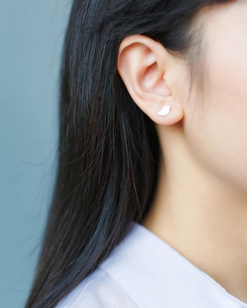Bird and Branch Mismatched Stud Earrings on ears