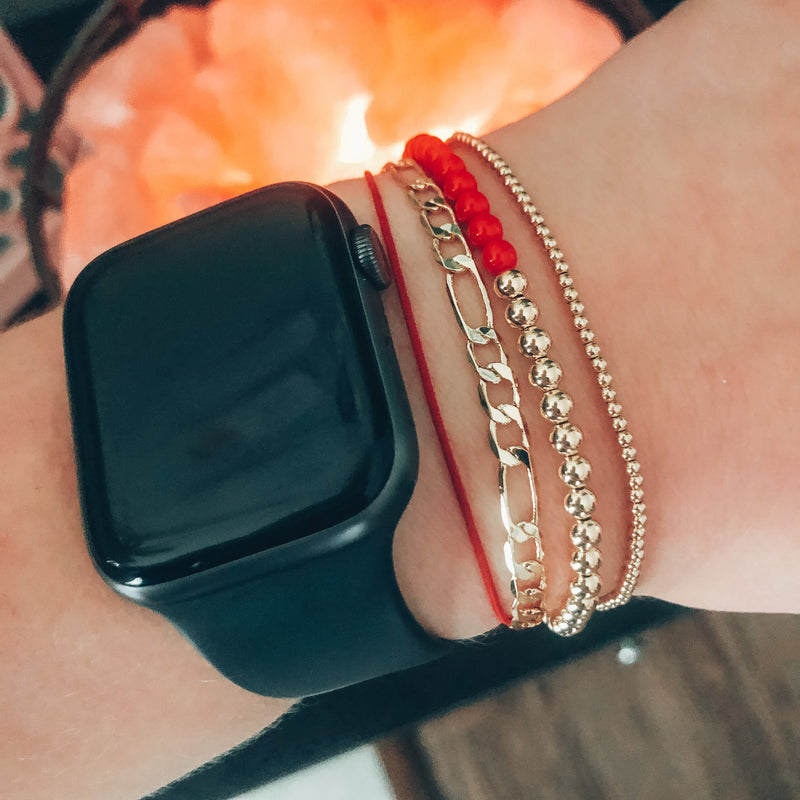 Model photo of wrist with stack of gold bracelets