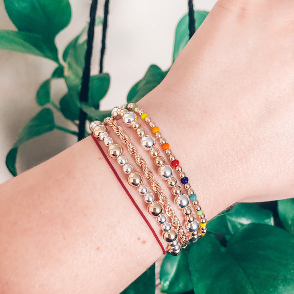 Model wearing stack of mixed metal bracelets, gold rope bracelet, and rainbow czech glass beaded bracelet