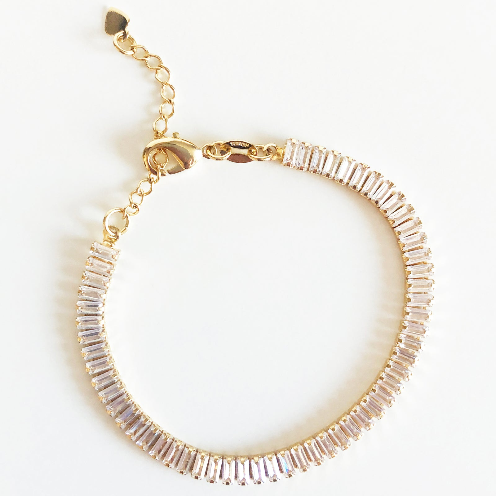 Gold bracelet with sparkling white rectangular stones with extender clasp