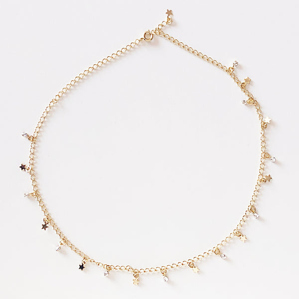 Gold necklace with stars and stones as charms