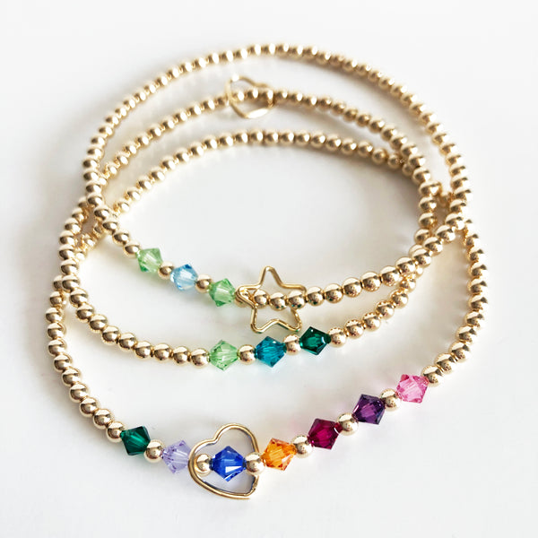 Stack of gold beaded Swarovski birthstone bracelets with charms