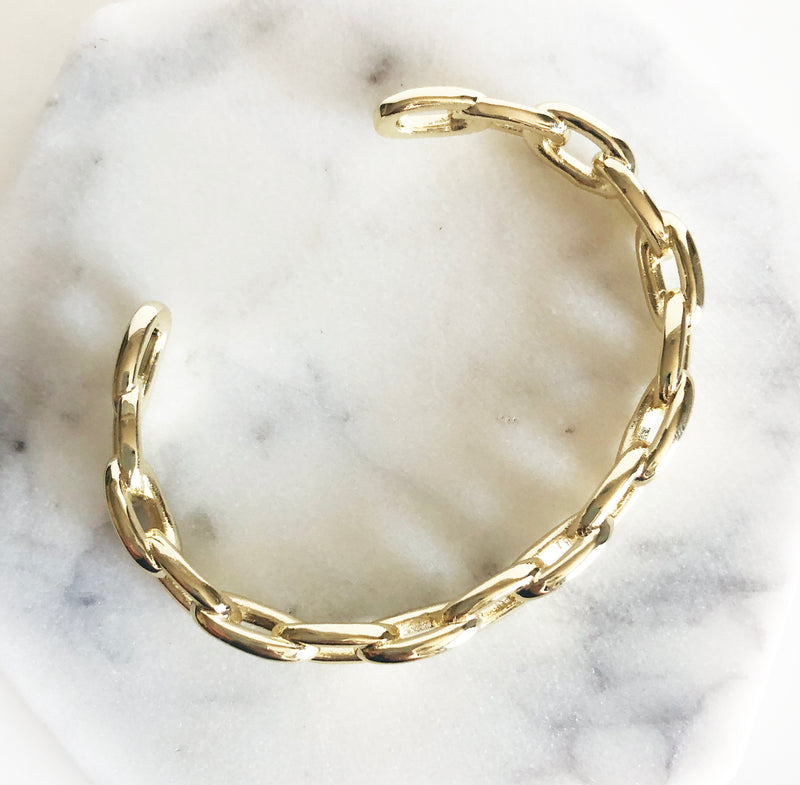 Chunky gold link chain cuff bracelet flat lay display
