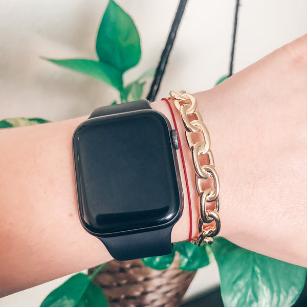 Model wearing chunky gold link chain cuff bracelet with stacked with Apple Watch