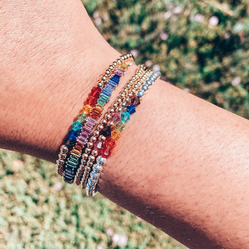 Model photo wearing stack of gold and rainbow colored beaded bracelets with Swarovski crystals