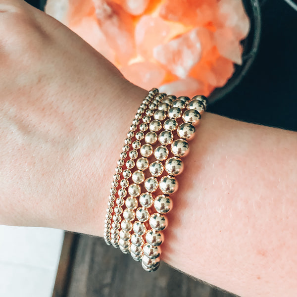 Model photo of wrist wearing a stack of gold beaded bracelets