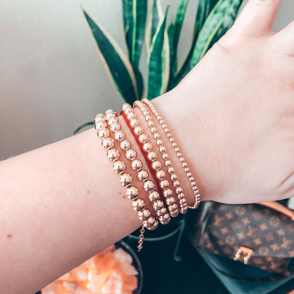 Model photo of wrist wearing stack of beaded gold bracelets
