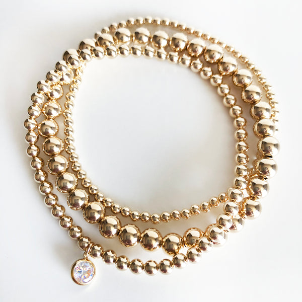 14K Gold-Filled beaded stack of bracelets with a round Swarovski crystal charm