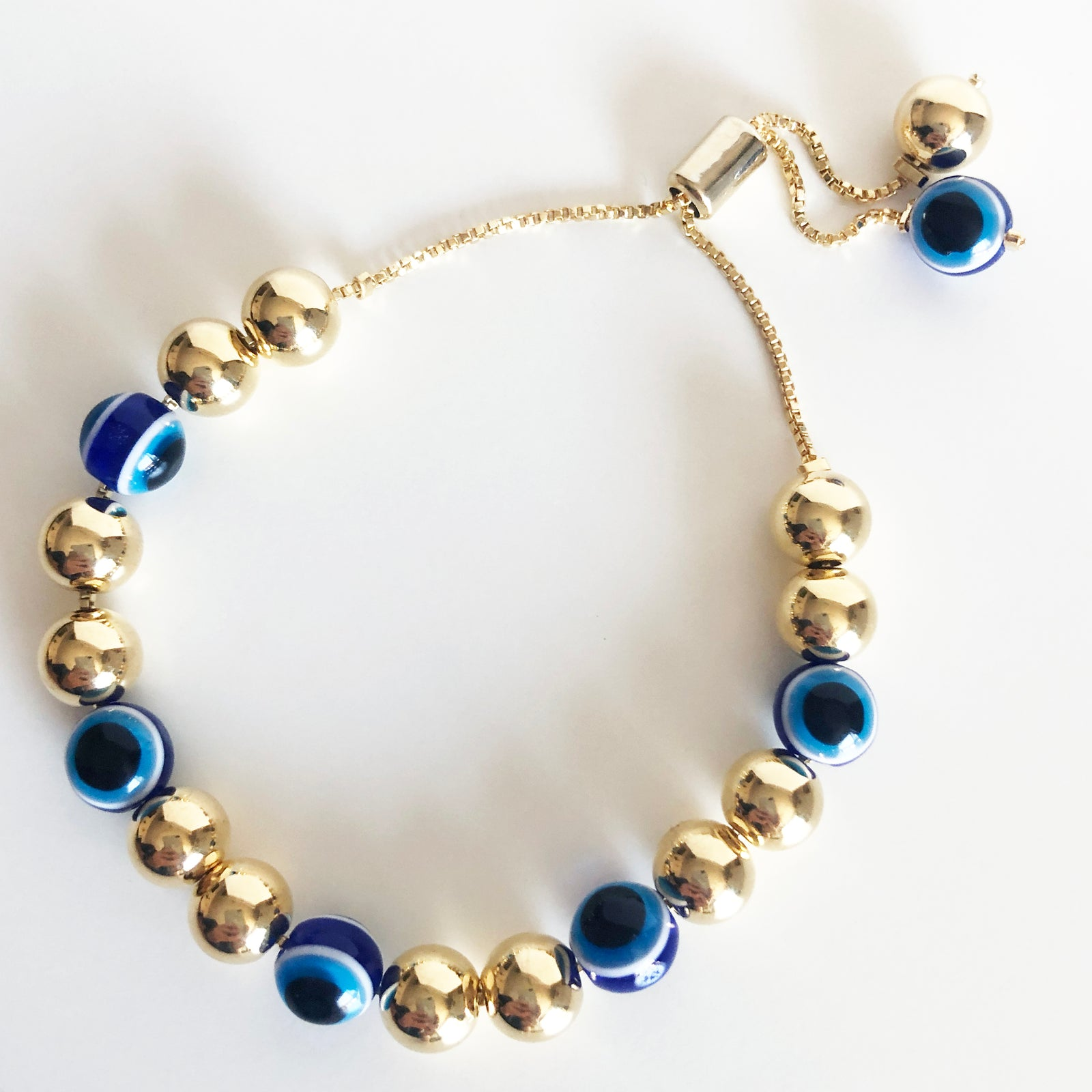 Alternating gold beads and evil eye beaded bracelet on a box chain with a bolo claps