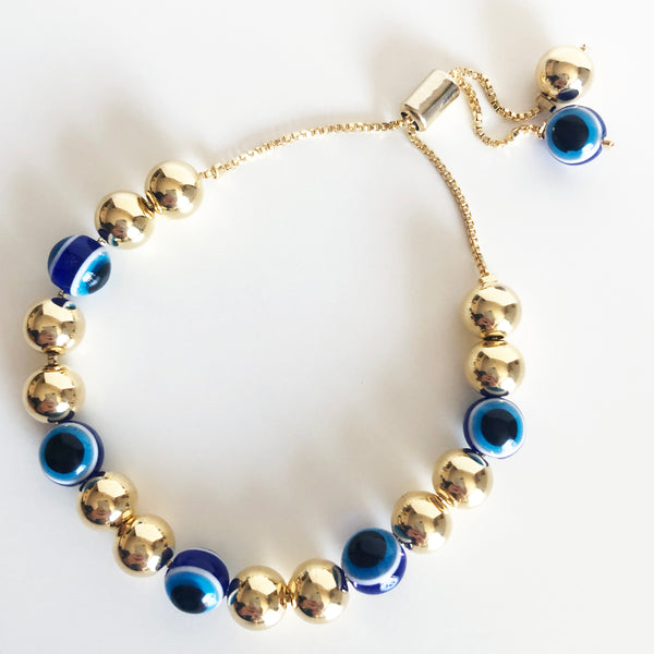 7mm alternating gold and evil eye beaded drishti bracelet with bolo closure on a box chain