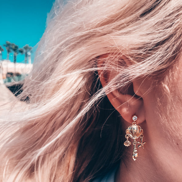 Model photo wearing CZ stud post with dangling seashell charms 14k gold-filled earrings