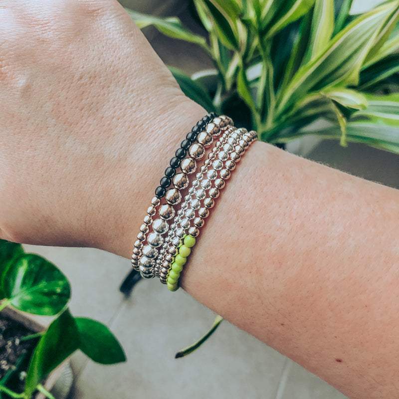 Model photo wearing triple stack of half 14k gold-filled and half sterling silver beaded bracelets in 3mm, 4mm, and 6mm bead sizes