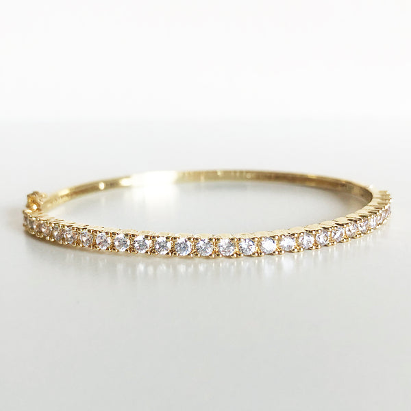 Gold and cubic zirconia latch-clasp bangle flat lay display