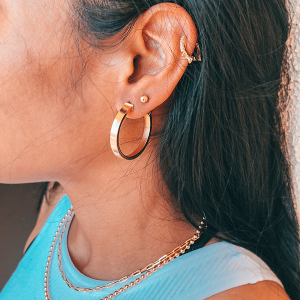 Model wearing layered gold jewelry, necklaces, gold chains, hoop earrings, stud in second earring hole and cartilage piercing