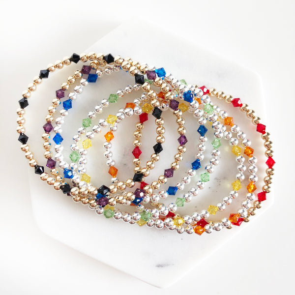 Stack of 14k gold-filled and sterling silver beaded bracelets with Swarovski crystals