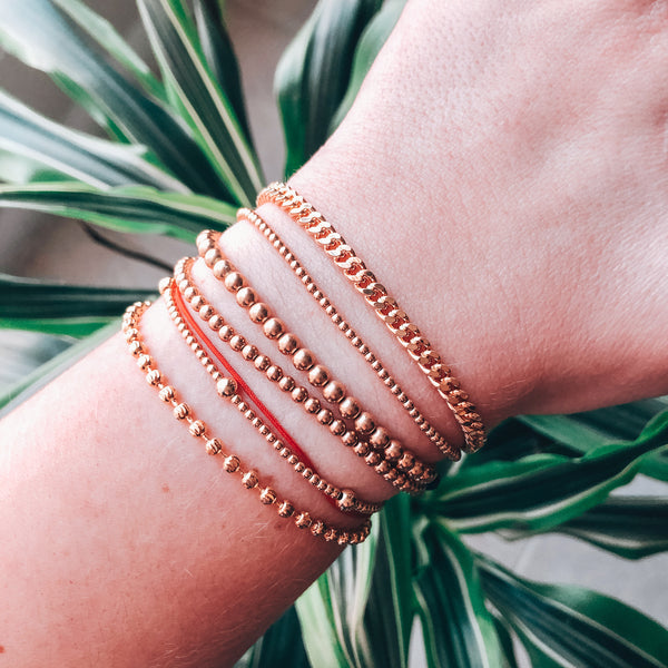 Model photo wearing a stack of classic gold bracelets including 14k gold-filled dainty minimal curb chain bracelet with extender