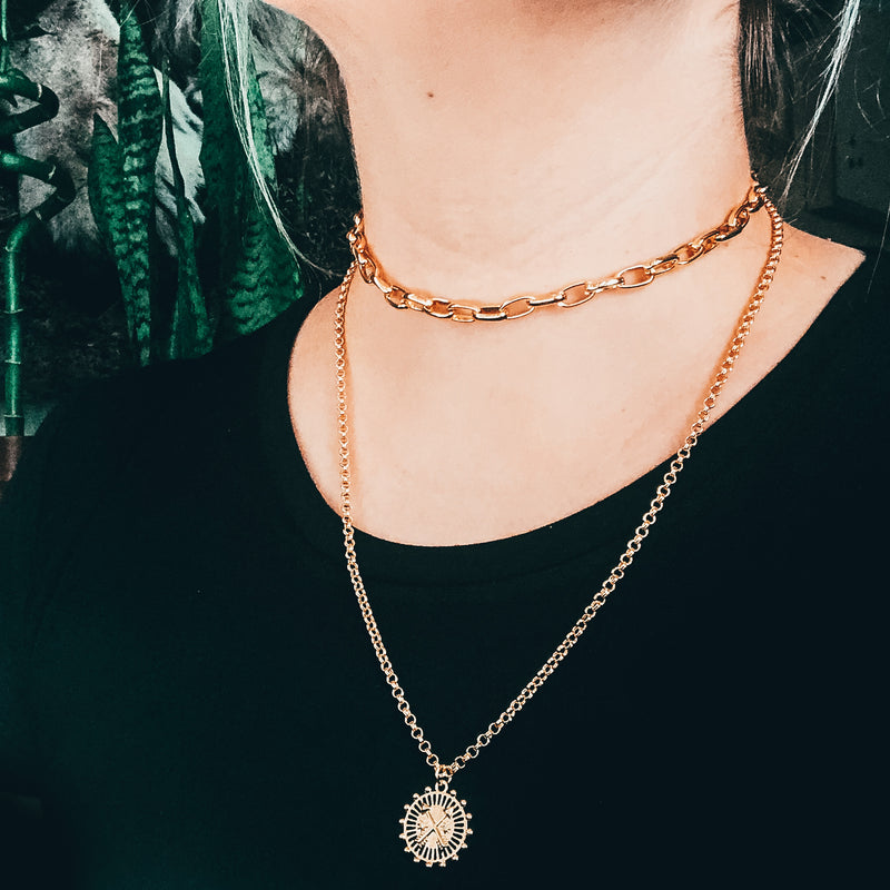 Model photo wearing layered gold necklaces including 14k gold-filled thick chain link choker necklace