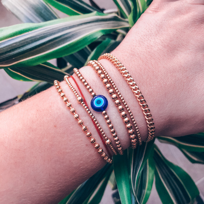 model photo wearing stacked bracelets including blue evil eye bead on 3mm 14k gold-filled beaded bracelet